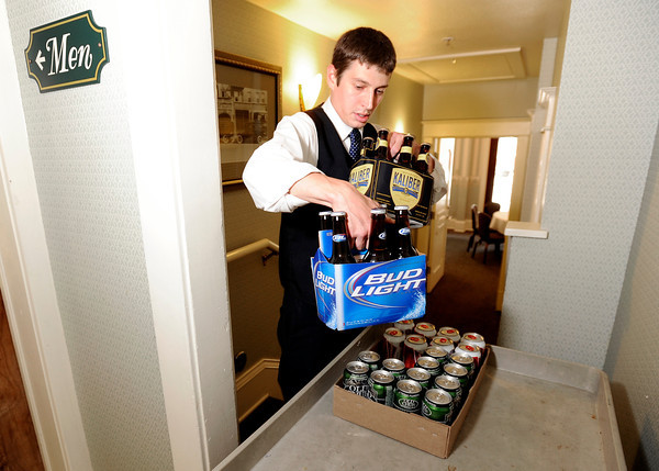 Hotel Boulderado employee Ryan Smith grabs a few six packs of beer while setting up for a hotel party on Thursday, May 3, in Boulder.<br /> Jeremy Papasso/ Boulder Daily Camera