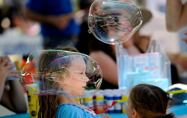 """Adenet Goldfeder, 6, dodges a large bubble she made while playing at the Mazel Tot booth during the Jewish Festival on the Pearl Street Mall in Boulder, Colorado June 12, 2011.  CAMERA/Mark Leffingwell<br /> <br /> Watch video from the Jewish Festival at  <a href=""""http://www.dailycamera.com"""">http://www.dailycamera.com</a>"""