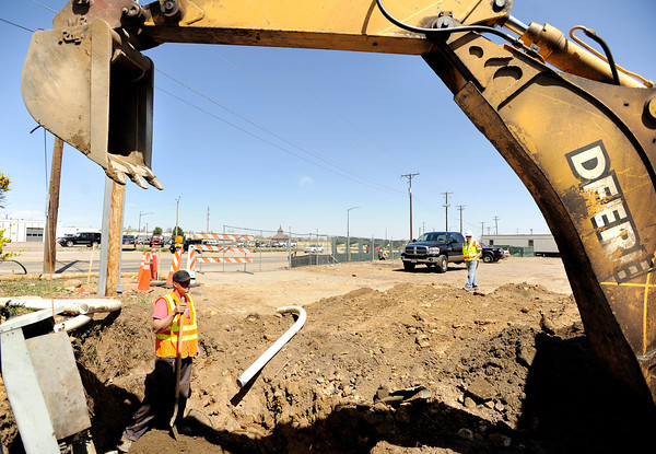 """Precision Directional Drilling employee Justin Coutts waits for more instructions while relocating a telephone pole on Friday, April 6, at the future site of the Boulder Junction apartments at 3100 Pearl Street. For more photos of the construction go to  <a href=""""http://www.dailycamera.com"""">http://www.dailycamera.com</a> Jeremy Papasso/ Camera"""