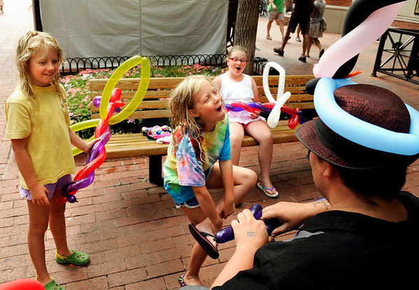 "Brittany Lilja, 8, center, goofs off with her sister Courtney, left, and her cousin Alexandra Lilja while Miles Modine makes them balloon art on Saturday, July 16, during the Open Arts Festival on the Pearl Street Mall in Boulder. For more photos and video of the festival go to  <a href=""http://www.dailycamera.com"">http://www.dailycamera.com</a><br /> Jeremy Papasso/ Camera"