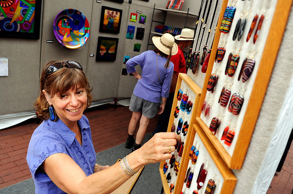 "Suzanne Chustz, of Santa Fe, N.M., hangs some of her custom made earings at her booth on Saturday, July 16, during the Open Arts Festival on the Pearl Street Mall in Boulder. For more photos and video of the festival go to  <a href=""http://www.dailycamera.com"">http://www.dailycamera.com</a><br /> Jeremy Papasso/ Camera"