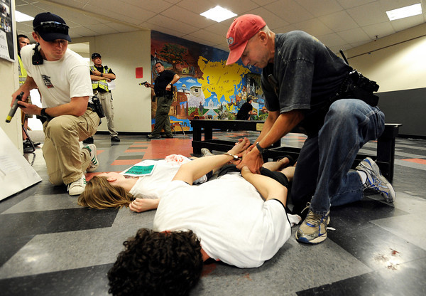 """Boulder Police Officer Kevin Granberg handcuffs a school shooting suspect during a training exercise for the Boulder Police Department on Thursday, June 21, at Fairview High School in Boulder. For more photos and video of the training exercise go to  <a href=""""http://www.dailycamera.com"""">http://www.dailycamera.com</a><br /> Jeremy Papasso/ Camera"""