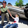 Elizabeth Ward looks up for backup as a volunteer victim cries for help next to an overturned car at the Police Training Scenario at Fairview High in Boulder, CO on  June 21, 2012.  <br /> Rachel Woolf/ Camera