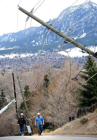 Power Company employees survey the scene of downed power poles on 19th Street in Boulder on Wednesday afternoon. <br /> Photo by Paul Aiken