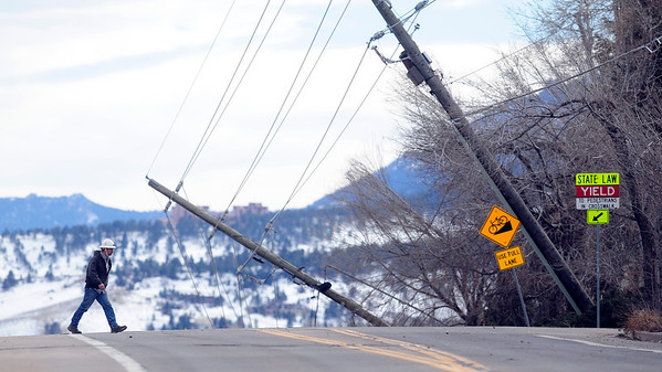 A Power Company employee surveys the scene of downed power poles on 19th Street in Boulder on Wednesday afternoon. <br /> Photo by Paul Aiken