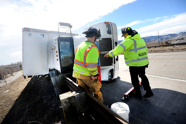 Boulder Firefighters prepare to try to stabilize a truck that overturned in high winds on the Foothills Highway overpass just north of Valmont Road on Wednesday afternoon. <br /> Photo by Paul Aiken