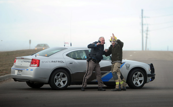A Colorado State Patrolmen and Boulder  County fireman, attempt to stand up in the wind at a roadblock at 63rd and the Diagonal.<br /> High wind gusts along Highway 119 from Boulder to Longmont resulted in overturned trucks and a grass fire on February 22, 2012.<br /> Cliff Grassmick / February 22, 2012