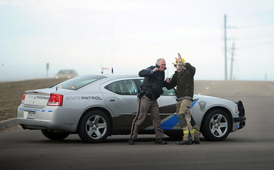 A Colorado State Patrolmen and Boulder  County fireman, attempt to stand up in the wind at a roadblock at 63rd and the Diagonal. High wind gusts along Highway 119 from Boulder to Longmont resulted in overturned trucks and a grass fire on February 22, 2012. Cliff Grassmick / February 22, 2012