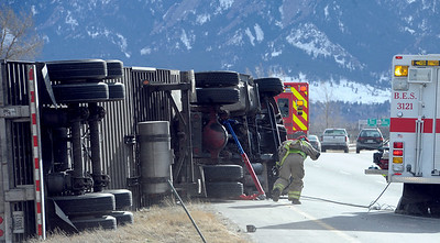 A large truck was blown over on Boulder-bound Highway 119 (Diagonal Highway). A fireman attempts to stand up in the high winds. High wind gusts along Highway 119 from Boulder to Longmont resulted in overturned trucks and a grass fire on February 22, 2012. Cliff Grassmick / February 22, 2012