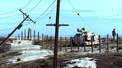 A power worker surveys the scene of a downed power line on Highway 93 just over the Jefferson County line