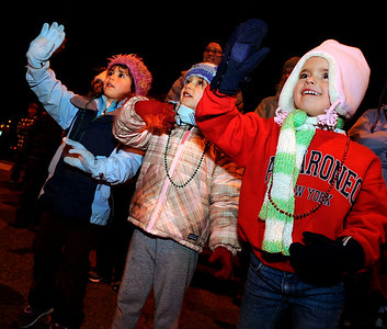Adelaide Obert, 4, right, Ruby Lortie, 5, and Delaney Watson, 4, smile and wave to Santa on Saturday, Dec. 4, during Boulder's Lights of December Parade in downtown Boulder. Jeremy Papasso/Camera