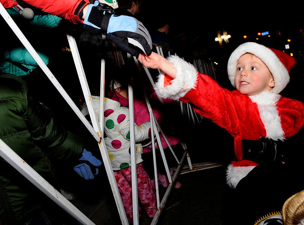 Connor Precourt, 4, of Erie, passes out candy to spectators while riding in his red wagon on Saturday, Dec. 4, during Boulder's Lights of December Parade in downtown Boulder.<br /> Jeremy Papasso/Camera