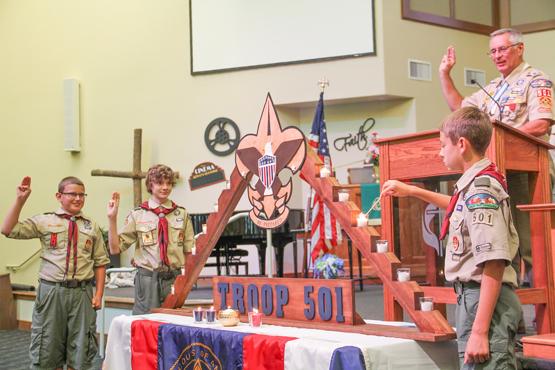 ALEC SMITH / GAZETTE Medina Boy Scout Troop 501 celebrates its 90th anniversary with ceremonies at Medina United Methodist Church. Shown from left are Marcus Koneval and Josh Reynolds, both 13, and at right lighting the candles that represent Scout law are Elliot Terrell, 13. Also participating but not shown was Aiden Dexheimer. At the podium is John Burke, Assistant Scoutmaster.
