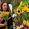 KRISTOPHER RADDER — BRATTLEBORO REFORMER<br /> Julie Cunningham inspects the sunflowers at Deer Ridge Farm at the Brattleboro Farmers Market on Saturday, 3, 2019.