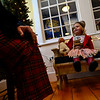 Daisy Altman, 2, sits on a bench and listens to Santa.