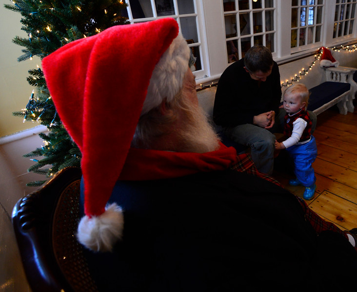 Mike Keim sits while his 15-month-old son Josiah looks upon Santa.