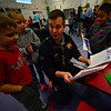 KRISTOPHER RADDER - BRATTLEBORO REFORMER<br /> Brattleboro Firefighter Matt Hubbard looks at pictures and notes written by first graders Dasan Severance, Layla Finley, and Azyi Cruz during a breakfast at the school with first responders on Wednesday, April 25, 2018.