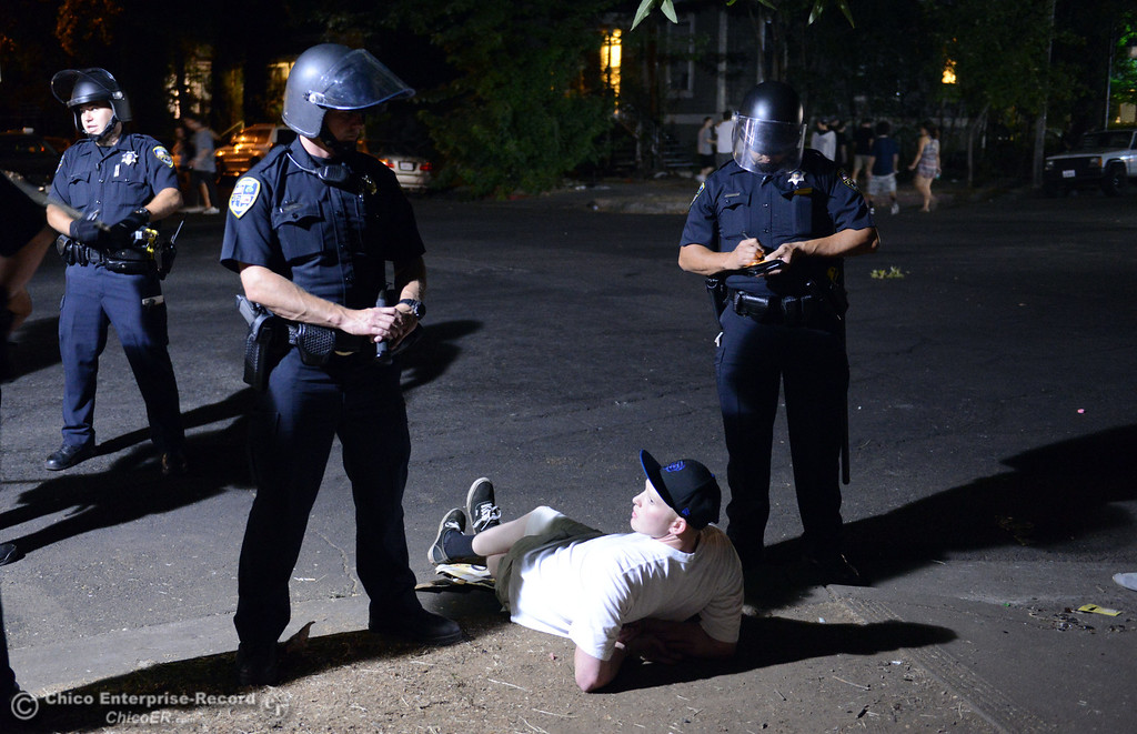 . Chico Police arrest a man after clearing a large gathering of people at W. 6th St. and Ivy St. after trying to get to a victim of a fight in the south campus area Friday, August 23, 2013 in Chico, Calif.  Police put on helmets after bottles were thrown at them. (Jason Halley/Chico Enterprise-Record)