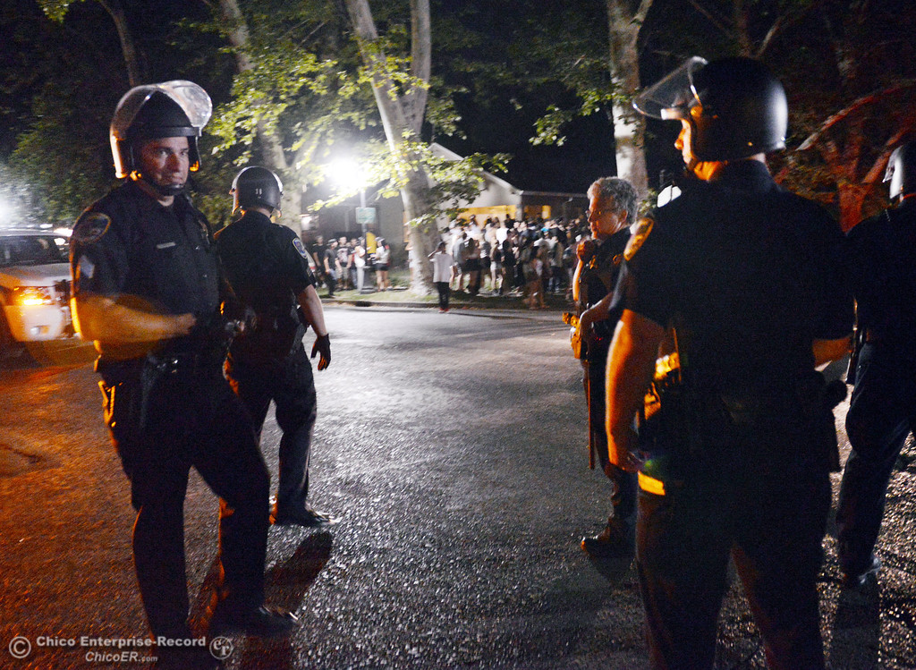 . Chico Police Sgt. Curtis Prosise (left) prepares to disperse crowds as they responded to large incidents and parties in the south campus area Friday, August 23, 2013 in Chico, Calif. Police wore helmets after bottles were thrown at them. (Jason Halley/Chico Enterprise-Record)