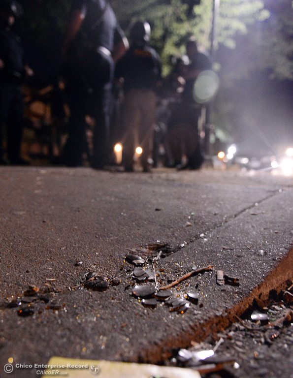 . Broken glass lies on the ground after Chico Police cleared a large gathering of people at W. 6th St. and Ivy St. after trying to get to a victim of a fight in the south campus area Friday, August 23, 2013 in Chico, Calif.  Police put on helmets after bottles were thrown at them. (Jason Halley/Chico Enterprise-Record)