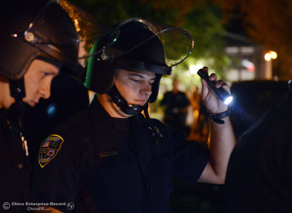 . Chico Police officer David Quigley (right) and others regrouped at the Notre Dame School parking lot to determine their response to large incidents in the south campus area Friday, August 23, 2013 in Chico, Calif. Police put on helmets after bottles were thrown at them. (Jason Halley/Chico Enterprise-Record)