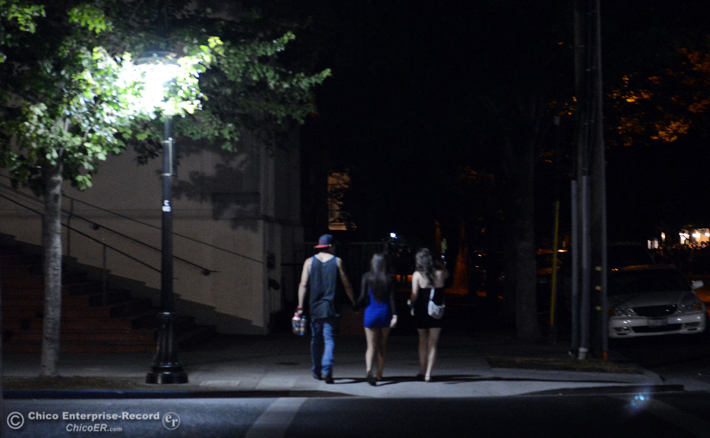 . People walk along W. 4th St. under a streetlight before Chico Police responded to large incidents in the south campus area Friday, August 23, 2013 in Chico, Calif.  (Jason Halley/Chico Enterprise-Record)