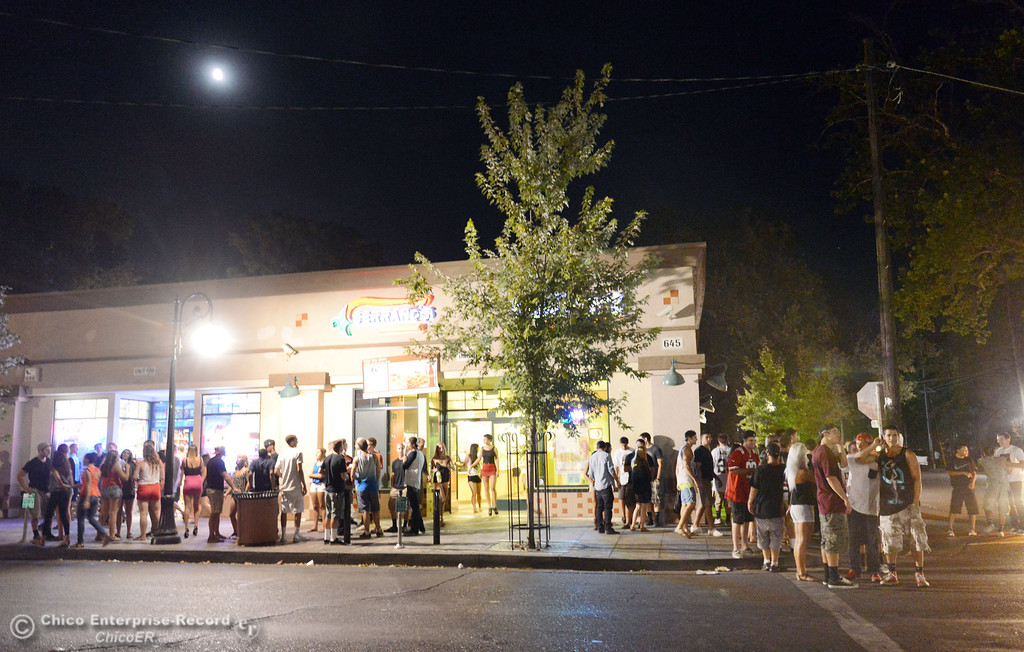 . People gather at a house on the corner of 5th St. and Ivy St. as Chico Police responded to large incidents in the south campus area Friday, August 23, 2013 in Chico, Calif.  (Jason Halley/Chico Enterprise-Record)