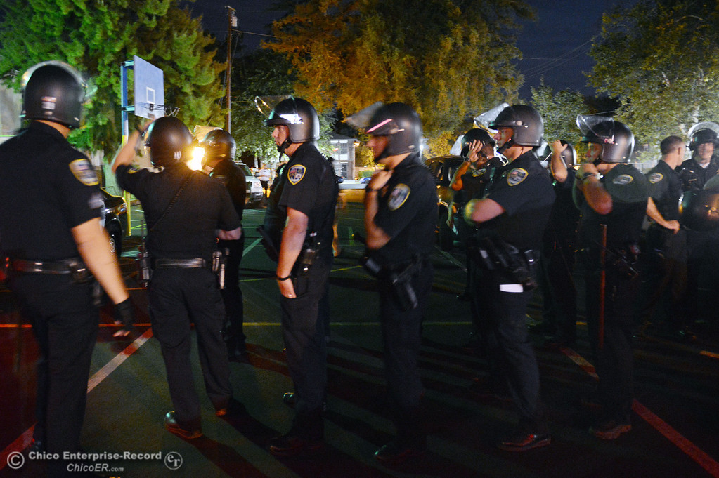 . Chico Police officers regrouped at the Notre Dame School parking lot to determine their response to large incidents in the south campus area Friday, August 23, 2013 in Chico, Calif. Police put on helmets after bottles were thrown at them. (Jason Halley/Chico Enterprise-Record)