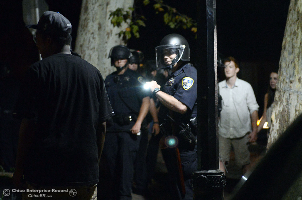 . Chico Police clear a large gathering of people at W. 6th St. and Ivy St. after trying to get to a victim of a fight in the south campus area Friday, August 23, 2013 in Chico, Calif.  Police put on helmets after bottles were thrown at them. (Jason Halley/Chico Enterprise-Record)