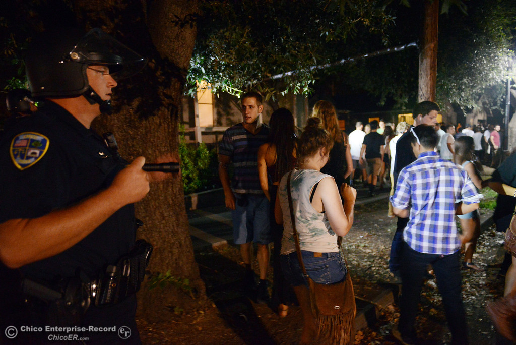 . Chico Police officers clear Ivy St. near W. 6th St of large crowds as they responded to incidents in the south campus area Friday, August 23, 2013 in Chico, Calif. Police put on helmets after bottles were thrown at them. (Jason Halley/Chico Enterprise-Record)