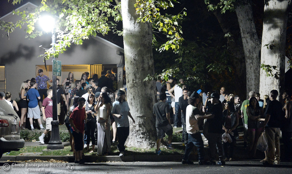 . People gather at a house on the corner of 6th St. and Ivy St. as Chico Police responded to large incidents in the south campus area Friday, August 23, 2013 in Chico, Calif.  (Jason Halley/Chico Enterprise-Record)