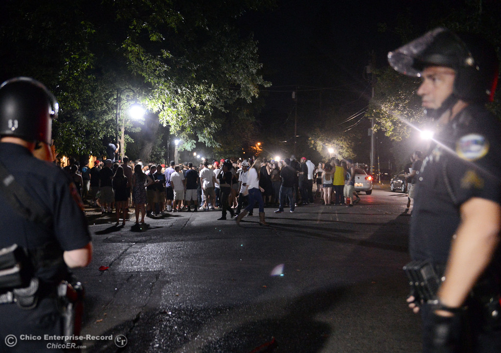 . People gather at W. 6th St and Ivy St. and Chico Police responded to large incidents in the south campus area Friday, August 23, 2013 in Chico, Calif.  (Jason Halley/Chico Enterprise-Record)