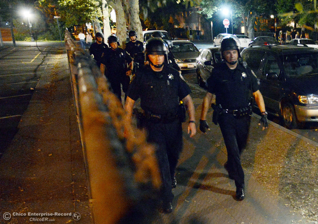 . Chico Police officer Peter Durfee (left) and Sgt. Curtis Prosise (right) lead a group from the Notre Dame School parking lot to respond to large incidents in the south campus area Friday, August 23, 2013 in Chico, Calif. Police put on helmets after bottles were thrown at them. (Jason Halley/Chico Enterprise-Record)