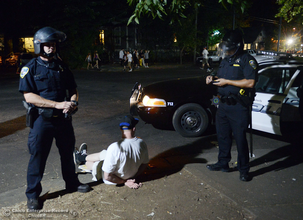 . Chico Police arrest a man after they cleared a large gathering of people at W. 6th St. and Ivy St. after trying to get to a victim of a fight in the south campus area Friday, August 23, 2013 in Chico, Calif.  Police put on helmets after bottles were thrown at them. (Jason Halley/Chico Enterprise-Record)