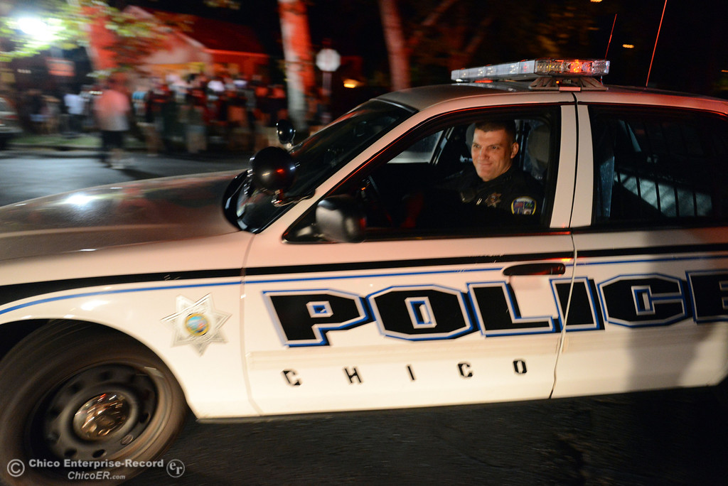 . Chico Police officer Tony Ferreira (left) responded to large incidents in the south campus area Friday, August 23, 2013 in Chico, Calif.  (Jason Halley/Chico Enterprise-Record)