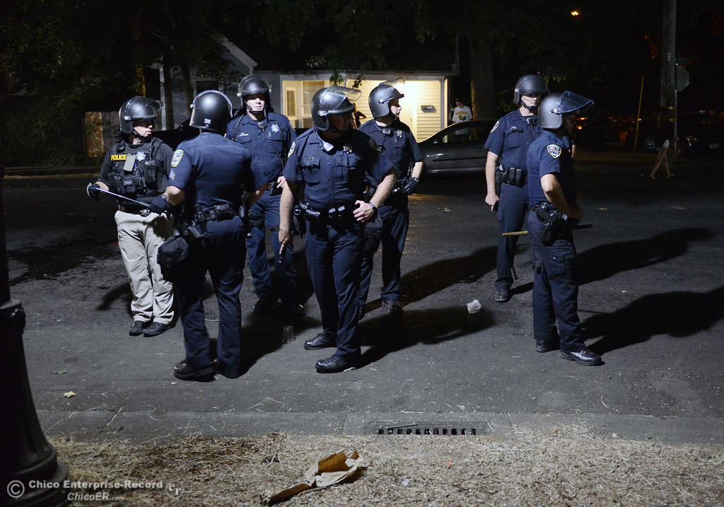 . Chico Police cleared a large gathering of people at W. 6th St. and Ivy St. after trying to get to a victim of a fight in the south campus area Friday, August 23, 2013 in Chico, Calif.  Police put on helmets after bottles were thrown at them. (Jason Halley/Chico Enterprise-Record)