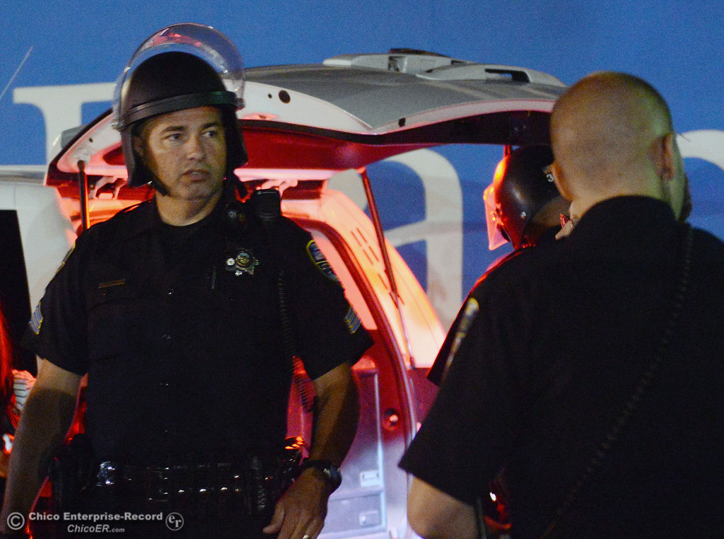 . Chico Police Sgt. Curtis Prosise regrouped at the Notre Dame School parking lot to determine their response to large incidents in the south campus area Friday, August 23, 2013 in Chico, Calif. Police put on helmets after bottles were thrown at them. (Jason Halley/Chico Enterprise-Record)