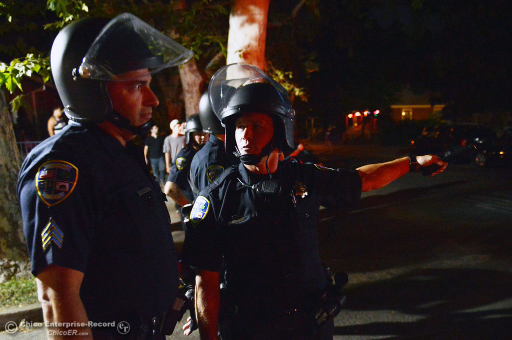 . Chico Police Sgt. Curtis Prosise (left) and officer Mike Caldwell (right) discuss what to do as they respond to a large gathering of people at W. 6th St. and Ivy St. in the south campus area Friday, August 23, 2013 in Chico, Calif.  Police put on helmets after bottles were thrown at them. (Jason Halley/Chico Enterprise-Record)