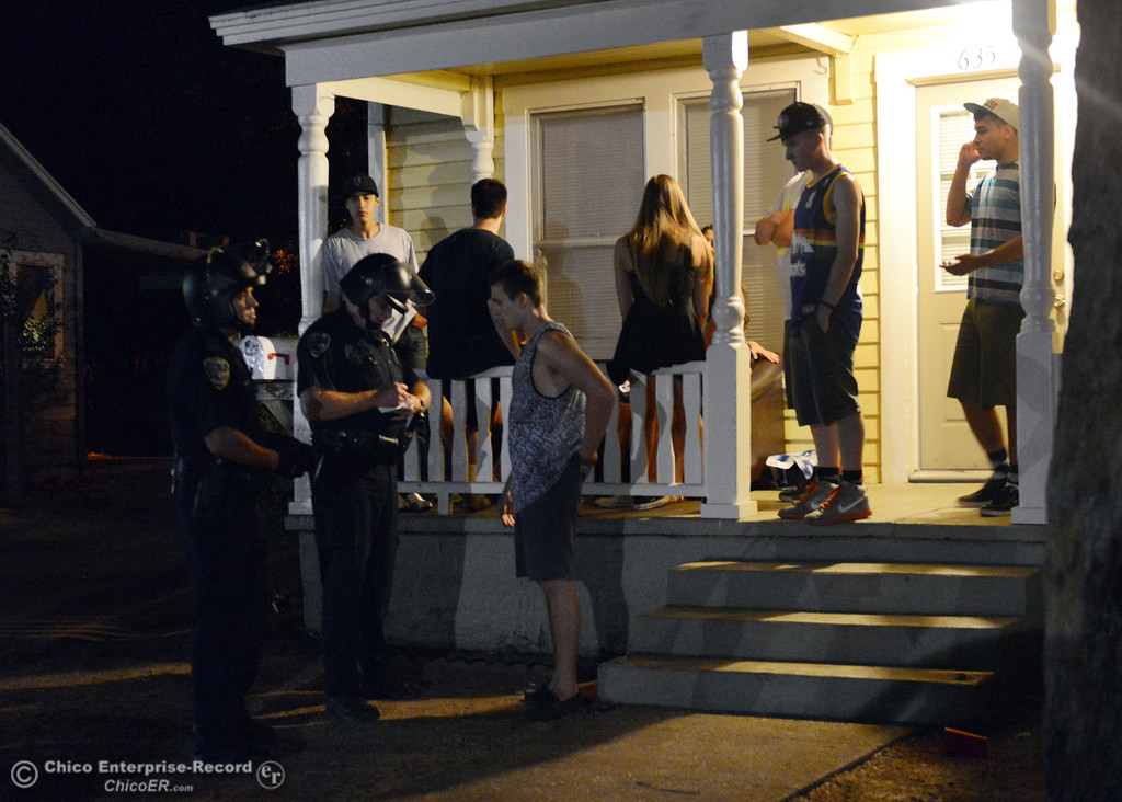 . Chico Police talk to residents at 635 Ivy St. in the south campus area Friday, August 23, 2013 in Chico, Calif.  Police put on helmets after bottles were thrown at them. (Jason Halley/Chico Enterprise-Record)