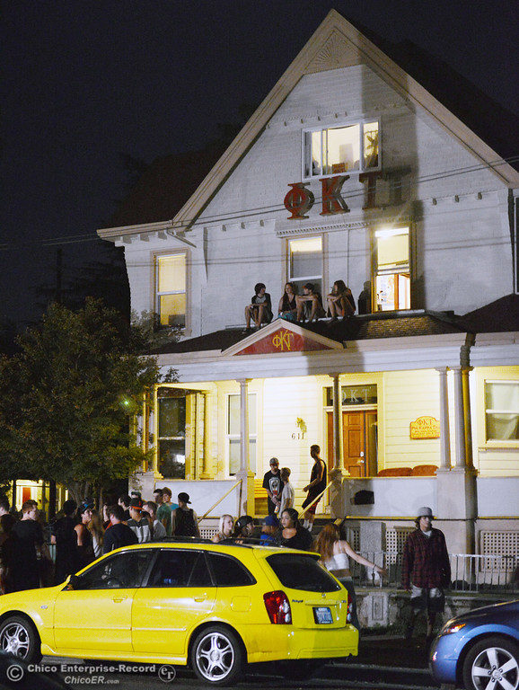 . People gather at a house along 5th St. near Hazel St. as Chico Police responded to large incidents in the south campus area Friday, August 23, 2013 in Chico, Calif.  (Jason Halley/Chico Enterprise-Record)