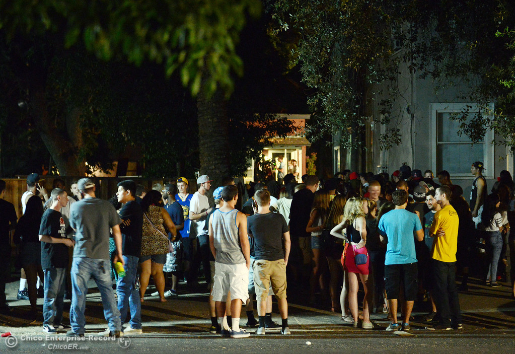 . People gather at a house along 5th St. near Ivy St. as Chico Police responded to large incidents in the south campus area Friday, August 23, 2013 in Chico, Calif.  (Jason Halley/Chico Enterprise-Record)