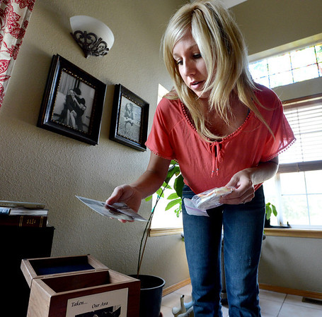 "Brittany Moore shows a photo and paw casting of her dog, Ava, kept in a box with the dog's ashes.<br /> Attorneys with the Animal Law Center announced they have filed a lawsuit against the town of Erie and Erie police Officer Jamie Chester on behalf of Brittany Moore, whose dog was shot and killed by Chester in 2011<br /> For more photos and a video of Moore, go to  <a href=""http://www.dailycamera.com"">http://www.dailycamera.com</a>.<br /> Cliff Grassmick / July 5, 2012"