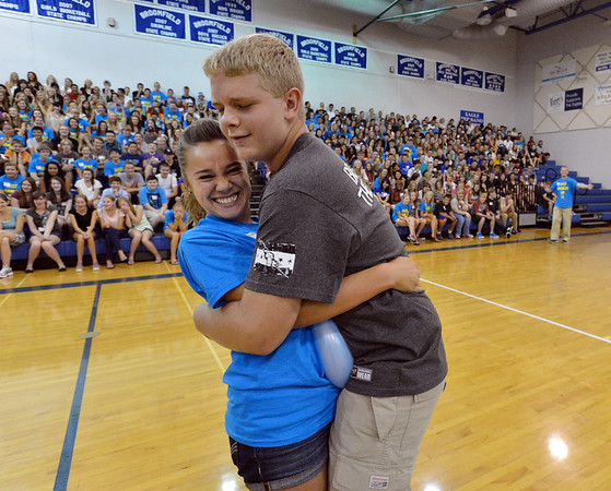 Upperclassman Matilda Whitemore, left, and freshman Mason O'Dell try to pop a balloon during the Blue Crew freshman orientation at Broomfield High School on Wednesday. <br />  August 15, 2012<br /> staff photo/ David R. Jennings