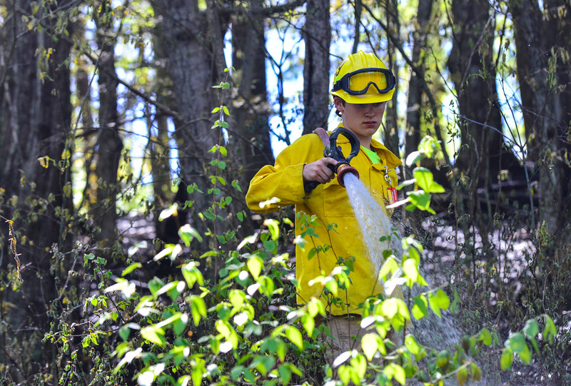 KRISTOPHER RADDER - BRATTLEBORO REFORMER<br /> A section of North Shore Road, in Spofford, N.H., is closed while fire crews from Spofford, Westmoreland, and Chesterfield battle a first-alarm brush fire on Friday, May 11, 2018. The fire is believed to be started by a dead tree that fell on a power line. The fire burnt nearly an acre and half of the land.
