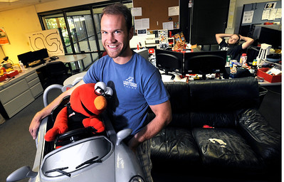 """_DSC1865A.JPG Nathan Seidle, CEO and Founder of Sparkfun with Elmo and car """"bot"""" he built for the company's Autonomous Vehicle Competition which the company sponsored this spring September 29, 2011. Competitors create a 'bot' that tried to navigate around the Sparkfun building without human intervention. Photo by Paul Aiken / September 262011"""