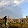 Chile Volcano.JPEG-094df.JPG A boy riding his bike looks at a plume of smoke and ash merging from the Puyehue-Cordon Caulle volcano in Rininahue near Lago Ranco, over 500 miles south of Santiago, Chile, Monday June 6, 2011. Authorities have evacuated about 3,500 people in the nearby area. The volcano was calm on Monday, two days after raining down ash and forcing thousands to flee, although the cloud of soot it had belched out still darkened skies as far away as Argentina. (AP Photo/Carlos Succo)
