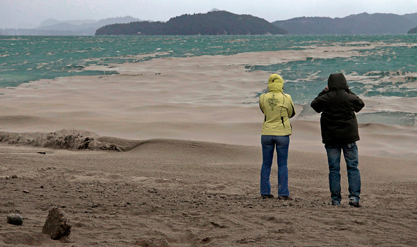 Argentina Chile Volcano(5).JPG Two people stand look out from the usually rocky lake shore, at the ash covered Nahuel Huapi lake, in San Carlos de Bariloche, southern Argentina, Tuesday June 7, 2011. The Puyehue volcano, dormant for decades, erupted in south-central Chile on Saturday. The wind carried ash across the Andes to Argentina, resulting in the closing of six airports, and dusting this tourist town. (AP Photo/Alfredo Leiva)