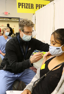Volunteers at Lowell General Hospital's vaccination site at Cross River Center in Lowell. Dr. Kirk MacNaught, M.D., of Andover, a cardiologist at LGH MVC Associates, vaccinates Malina Sar of Dracut.  JULIA MALAKIE/LOWELLSUN