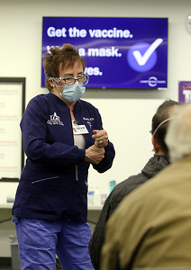 Volunteers at Lowell General Hospital's vaccination site at Cross River Center in Lowell. Retired LGH nurse Michelle Ratty, R.N., of Tyngsboro, chats with people as she monitors the room where people wait 15 minutes after receiving their vaccinations.  JULIA MALAKIE/LOWELLSUN