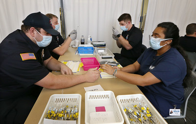 Volunteers at Lowell General Hospital's vaccination site at Cross River Center in Lowell. Tyngsboro firefighter/EMT Matthew Andrews of Tyngsboro, left, and Meghana Yellanki of Westford, Dartmouth Class of 2020, who is applying to medical school, label syringes after they're filled, as Tyngsboro FD Lt. John Pelletier, left rear, and firefighter Tom Geoffroy of Tyngsboro draws vaccine into syringes.  JULIA MALAKIE/LOWELLSUN